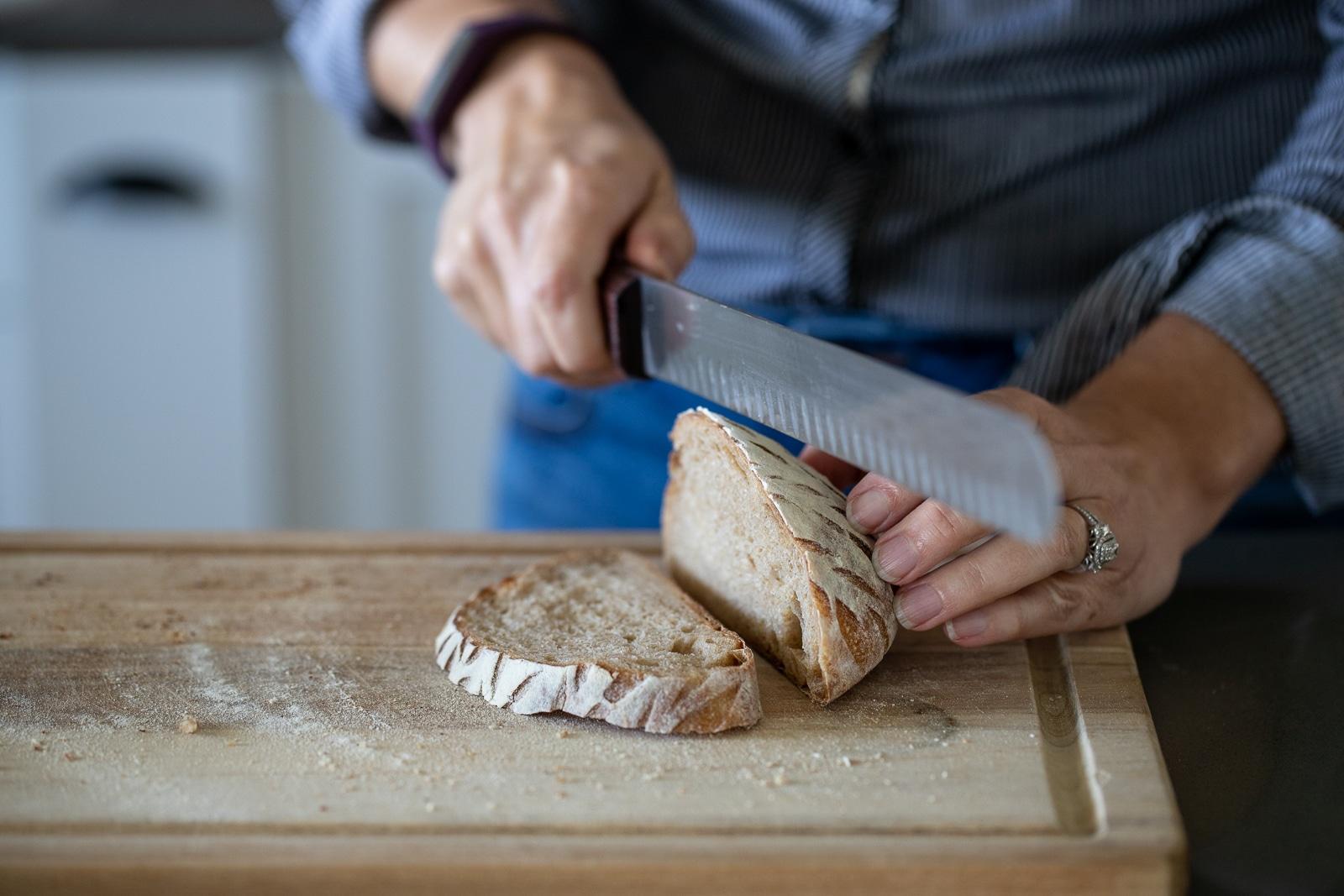 woman slicing sourdough bread on a wood cutting board.