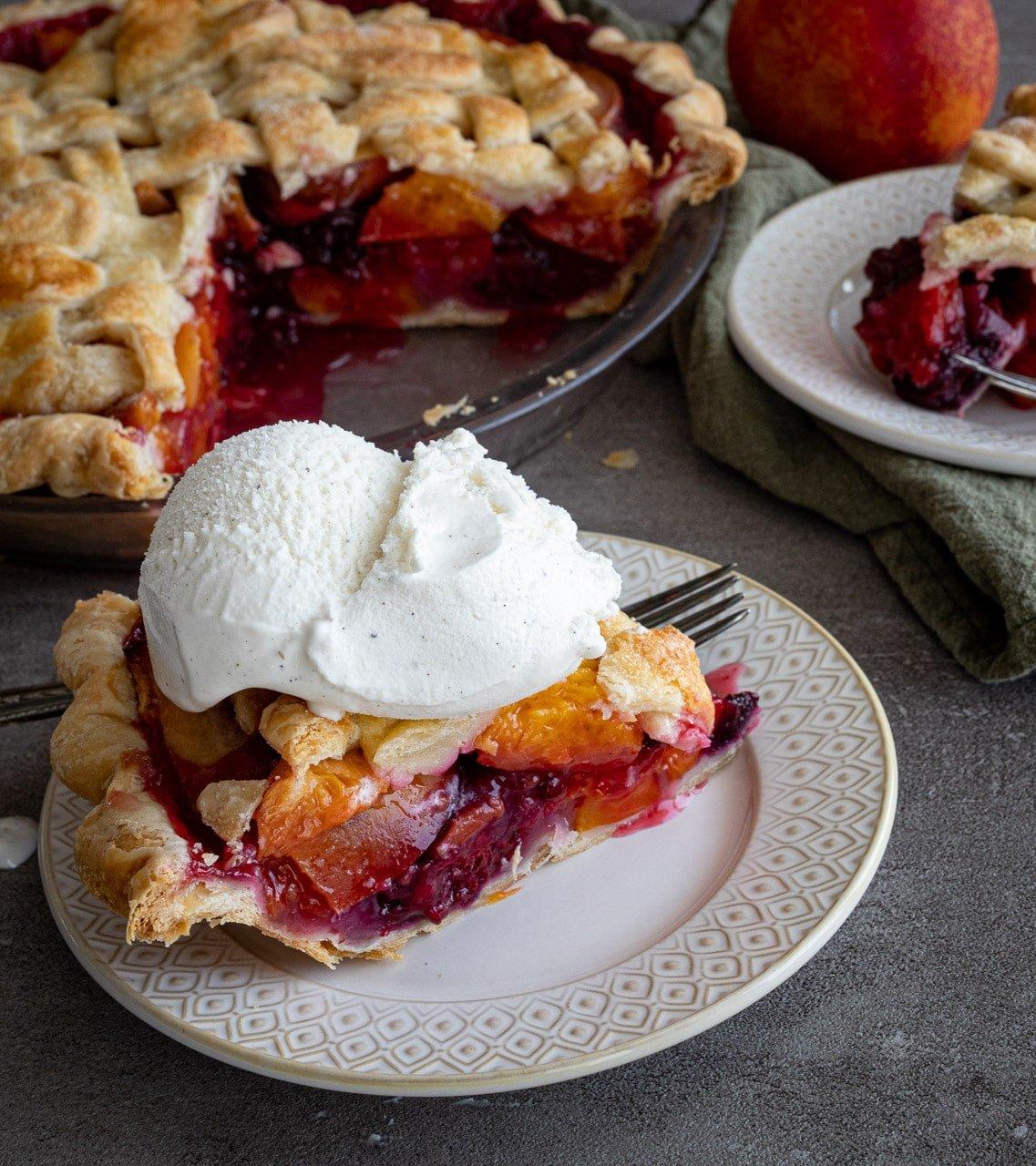 Nectarine and Blackberry Homemade Pie slice on a plate with vanilla ice cream