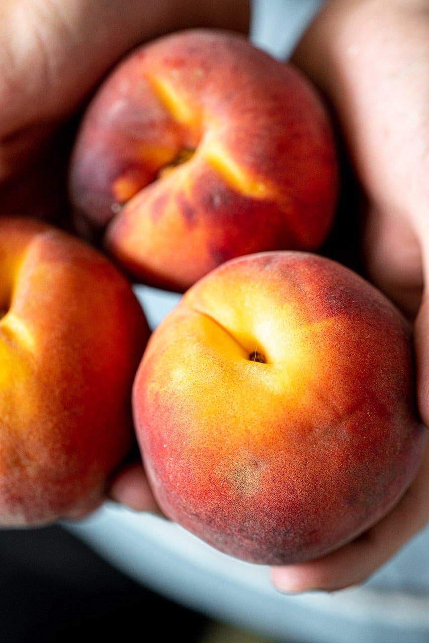 Fresh peaches in hands