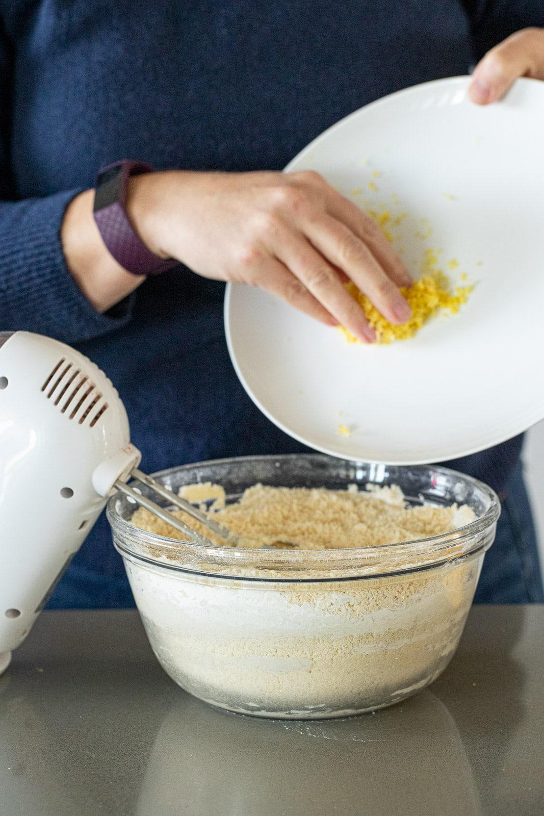 woman adding lemon zest to cookie batter