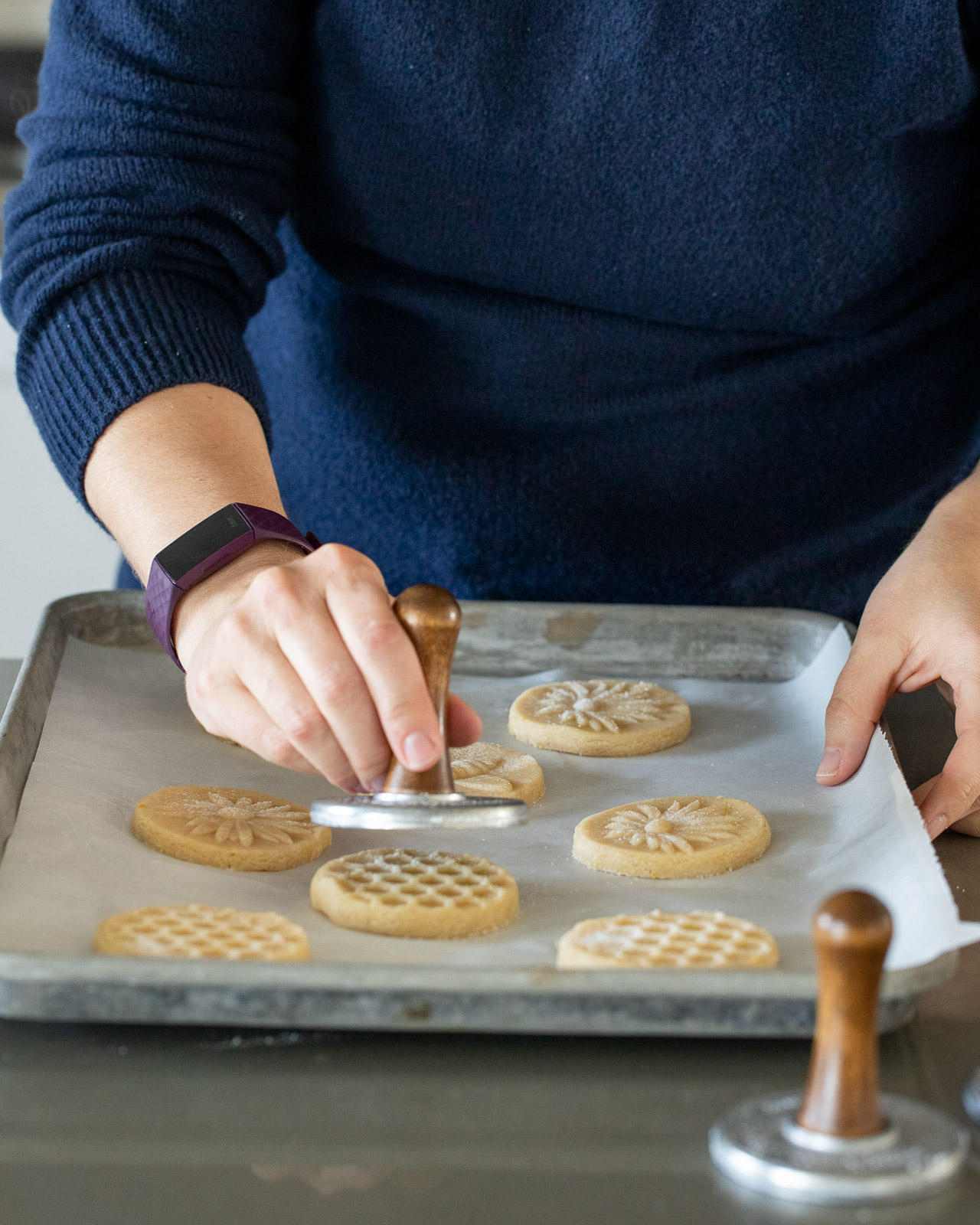 woman stamping cookies with nordicware stamp