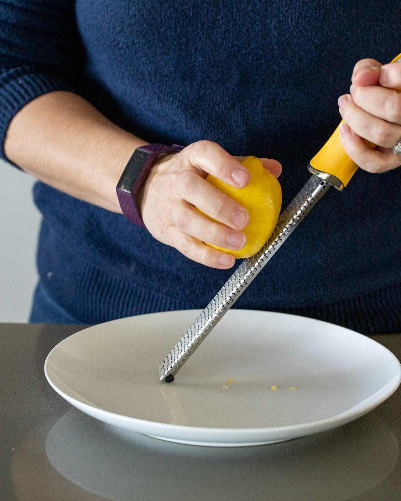 woman zesting lemon onto a plate