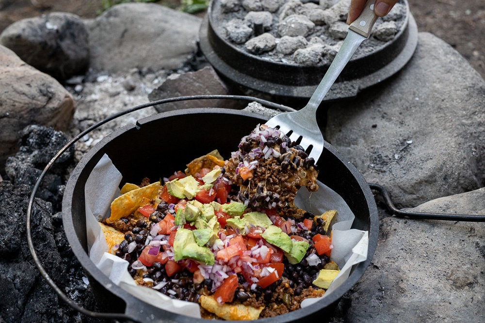 Simple to make dutch oven nachos in a firepit at a campsite.
