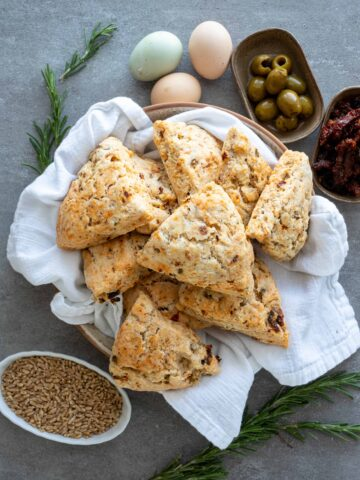 Sun dried tomato scones with green olives in a white serving dish.