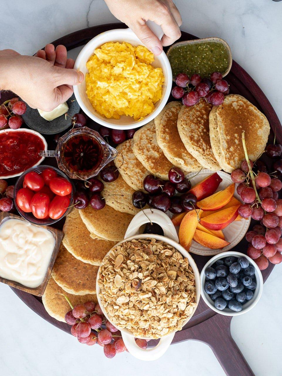 woman adding scrambled eggs to a breakfast charcuterie board.