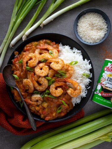 Creole Shrimp and sausage in a black bowl with white rice.