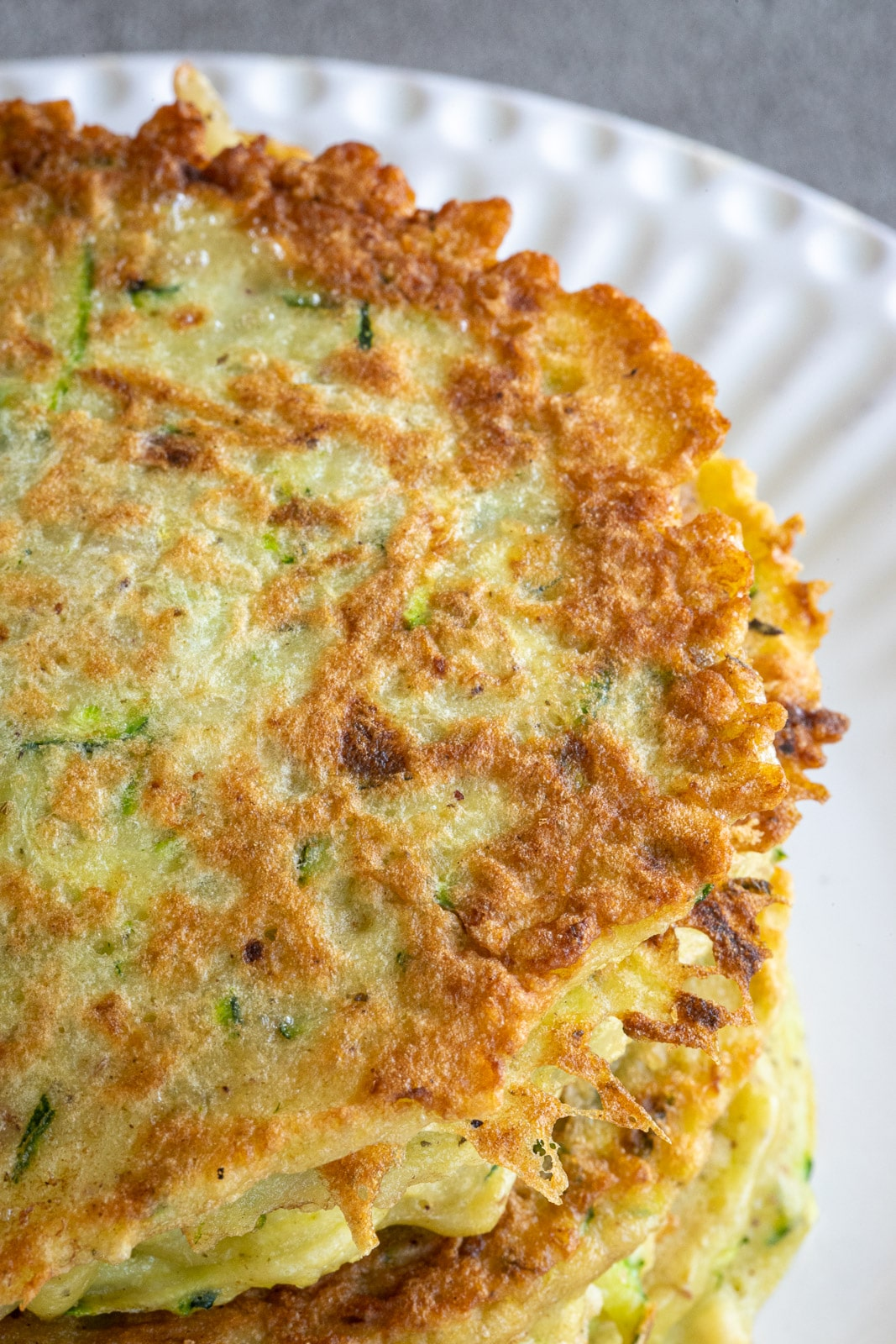 Stack of veggie fritters on a plate.