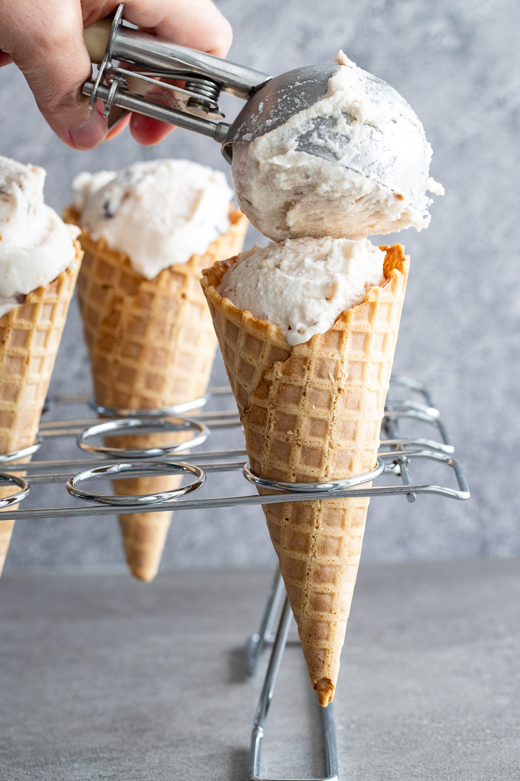 scooping dairy-free coconut ice cream onto a waffle cone with a cookie scoop.