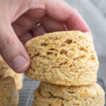 woman grabbing whole wheat biscuits from a cooling rack.