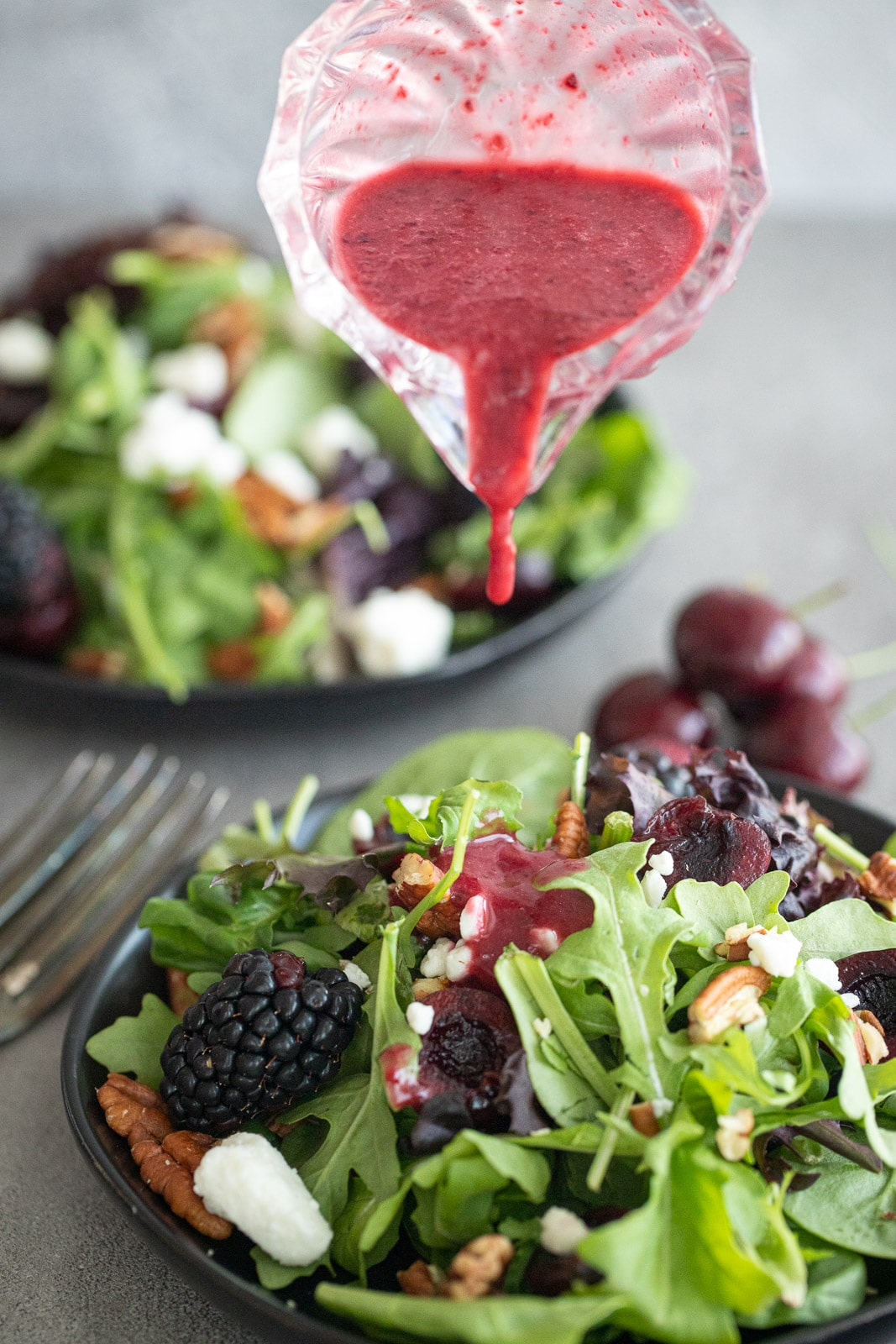 Woman adding cherry vinaigrette to a green salad with fruit.