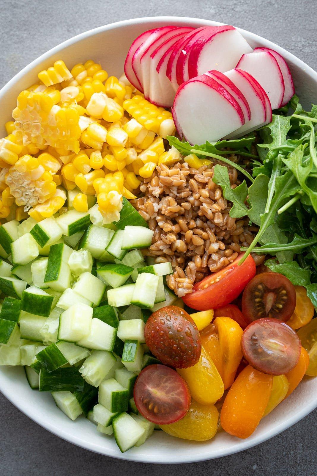 Vegetarian whole grain salad in a white bowl.