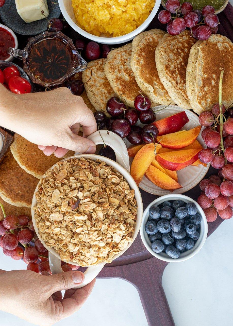 woman adding healthy granola to a breakfast charcuterie board.