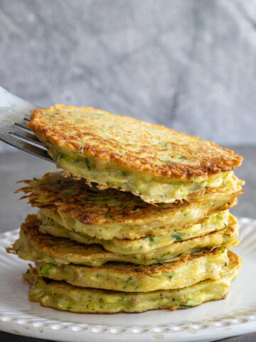 Woman adding a healthy zucchini potato fritter to a stack of fritters on a white plate.