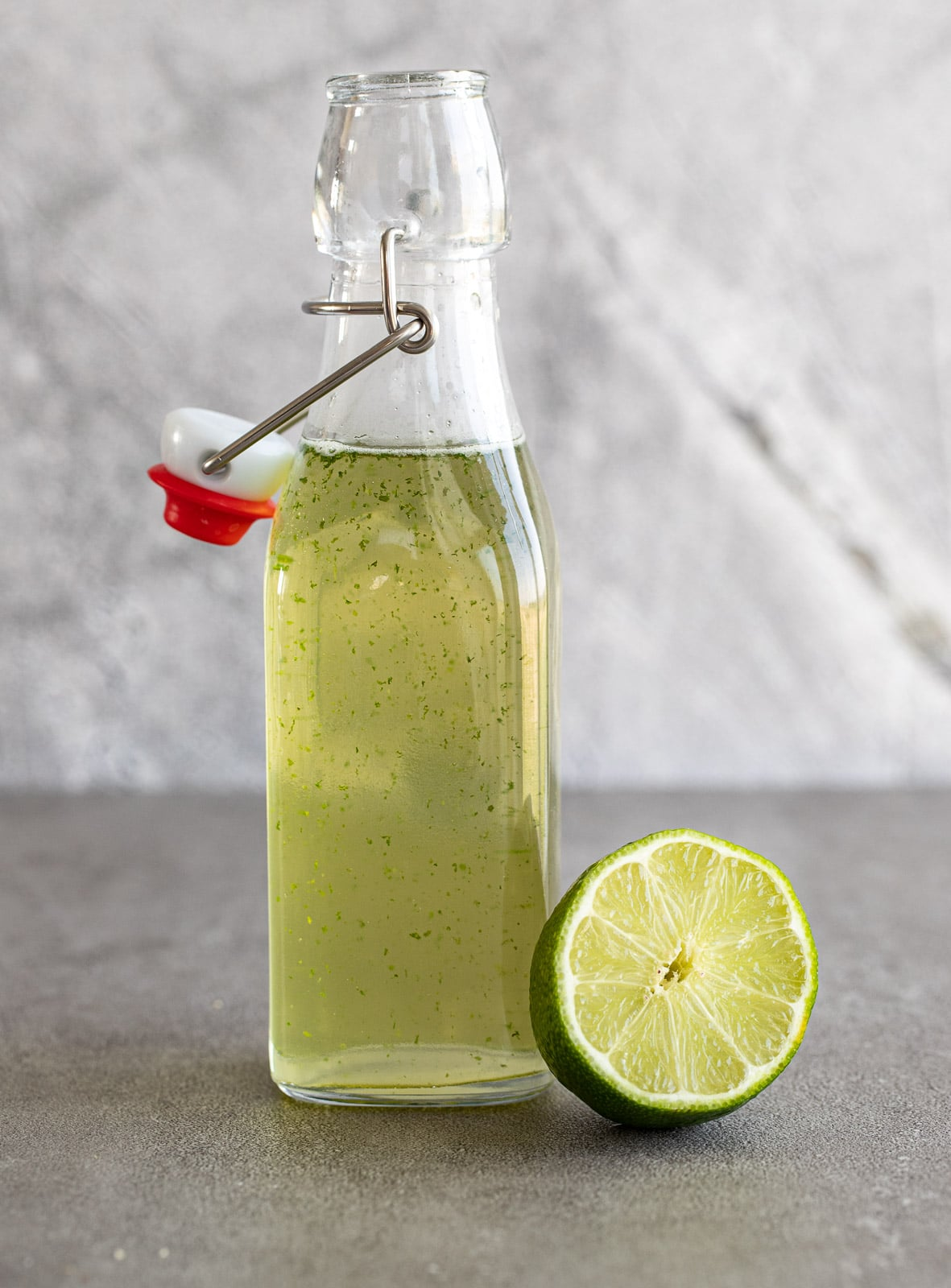lime simple syrup in a glass jar with stopper.