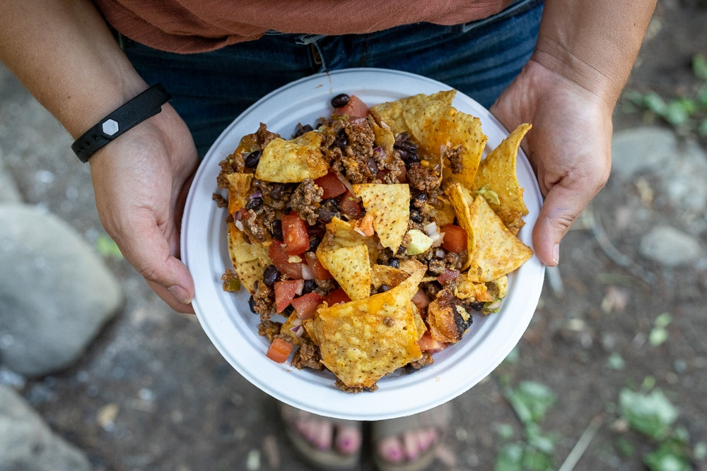 Simple to make dutch oven nachos on a white disposable plate.