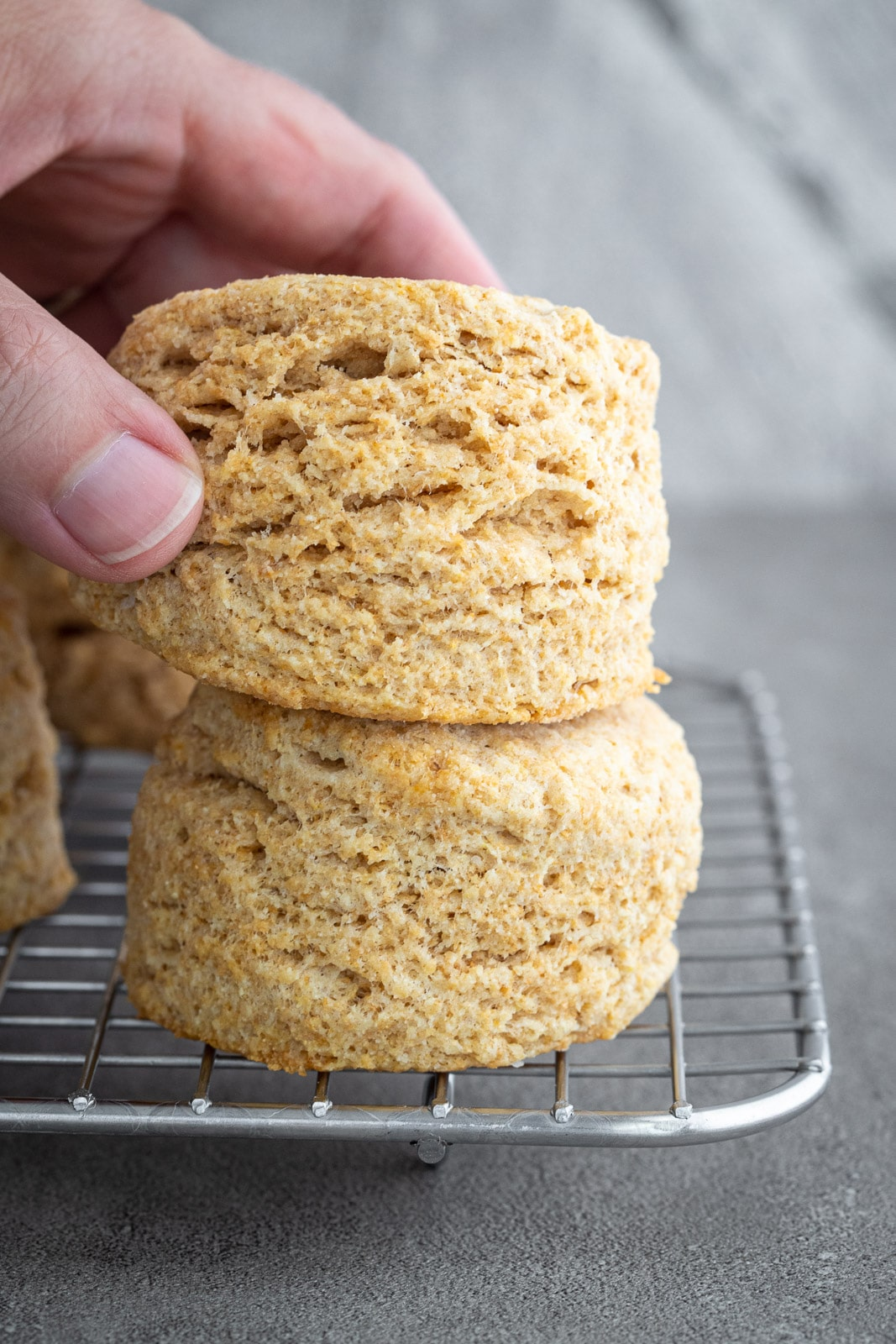 woman picking up whole wheat biscuits off a small cooling rack.
