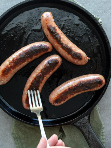 Cooked chicken sausage in a cast iron skillet.