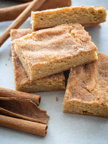 Simple Snickerdoodle Bars in a stack on parchment paper.