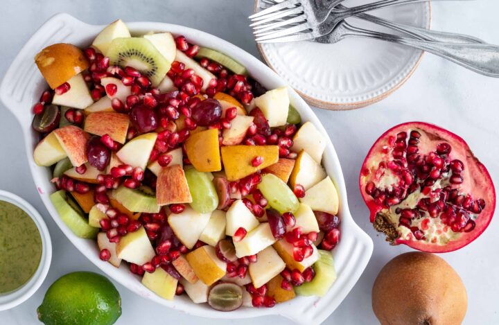 Fall fruit salad in a bowl with limes pomegranates and pears on the side.