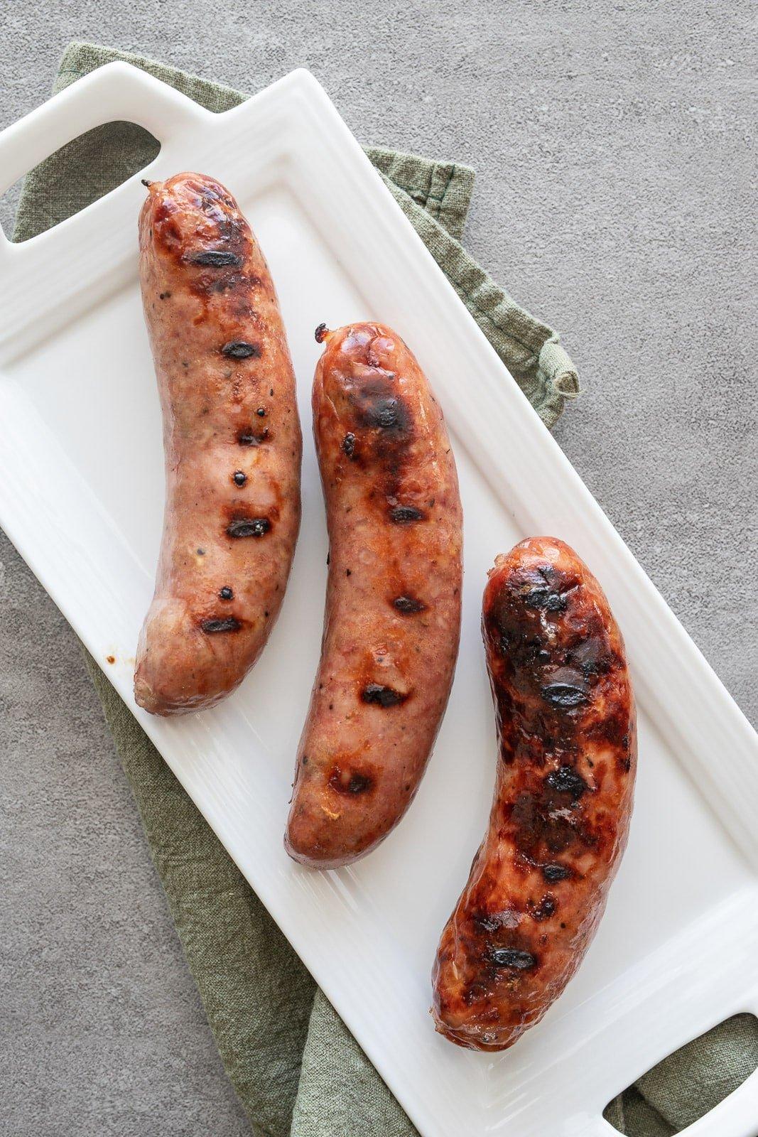 Grilled chicken sausage on a white platter.