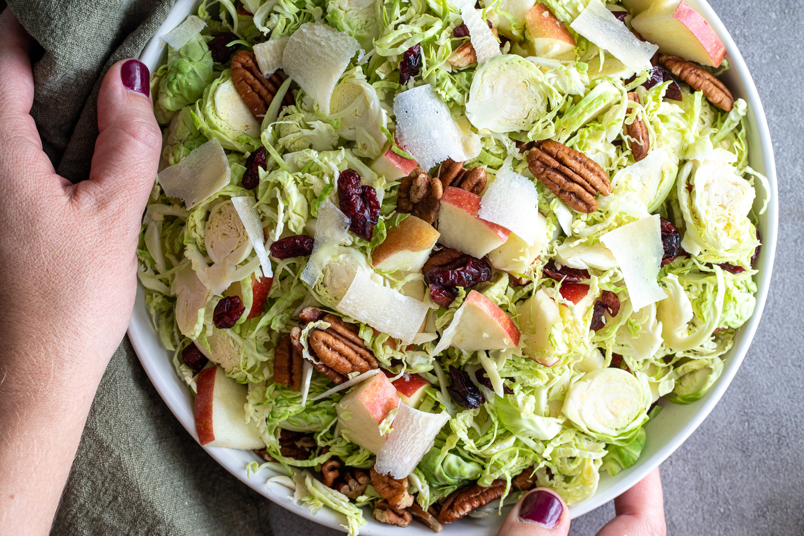 Shaved Brussel Sprouts Salad with Maple Dressing in a large white bowl.