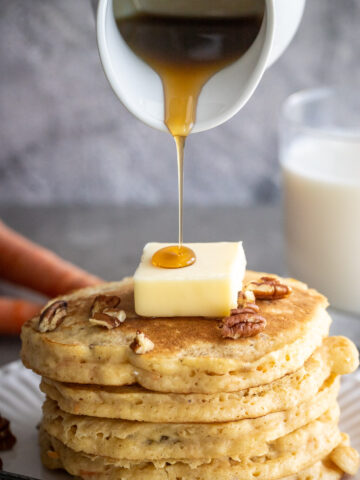 Woman pouring pure maple syrup on a stack of carrot cake pancakes.