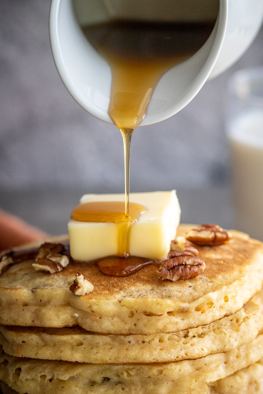 Pouring pure maple syrup on a stack of healthy carrot cake pancakes.