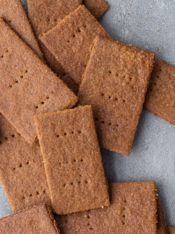 Vegan graham crackers in a pile on a surface.