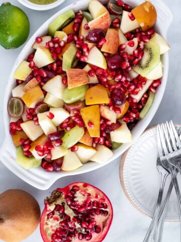 Easy fall fruit salad in a dish with small plates and forks to the side.