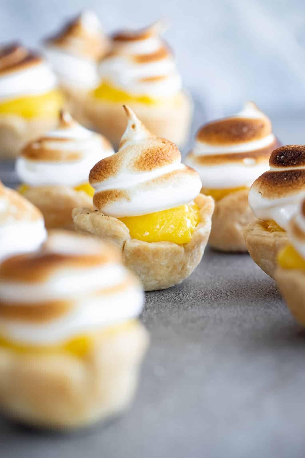 Mini Lemon Meringue Pies on set together on a surface.