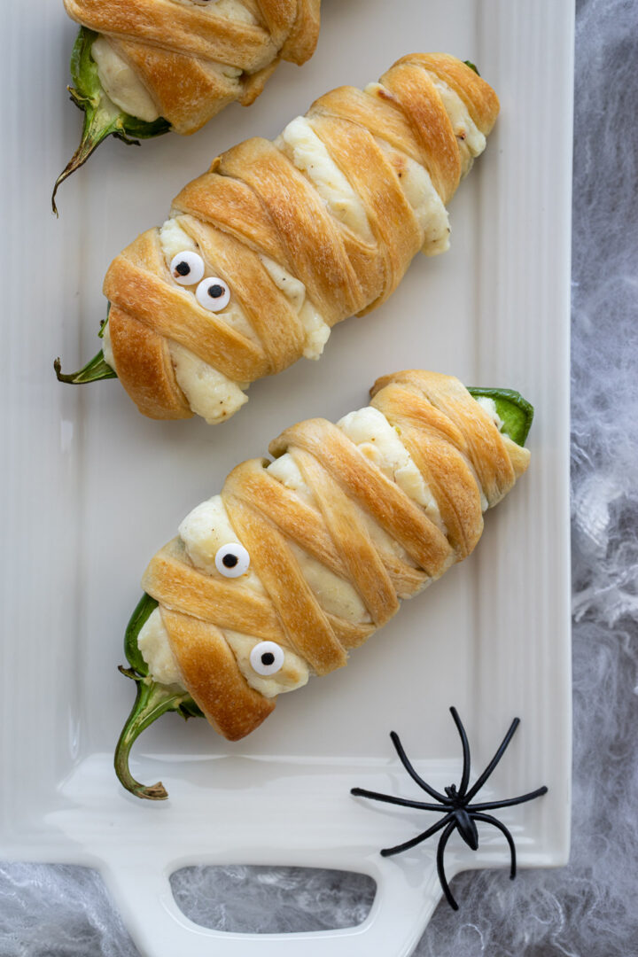 Easy Mummy Jalapeno Poppers for Halloween on a white tray with spiders on it.
