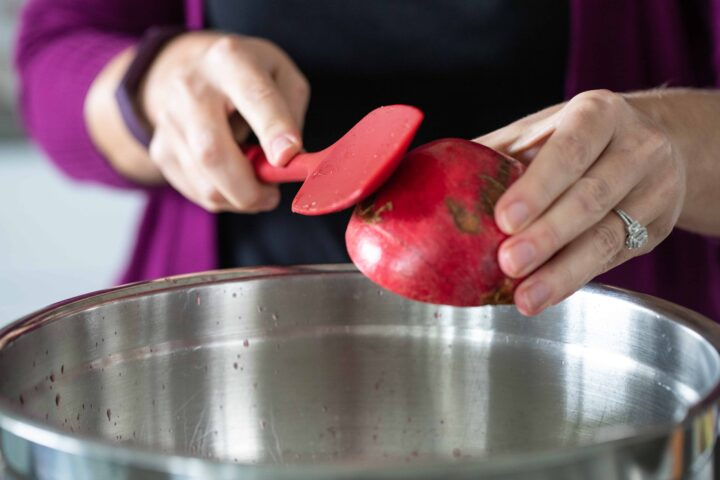 Woman knocking pomegranate seeds out with a rubber spatula.