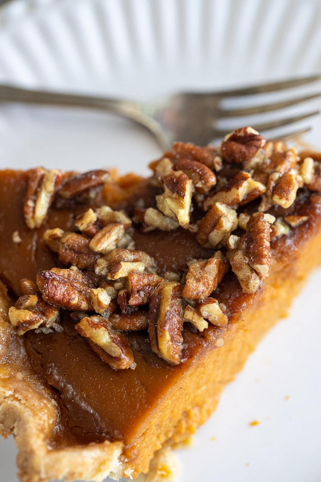 Slice of praline pumpkin pie on a plate.
