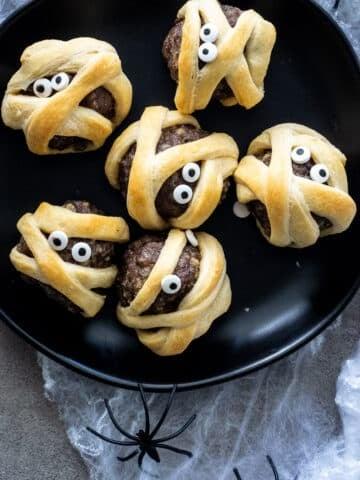 Simple Meatball Mummies For Halloween on a black plate.