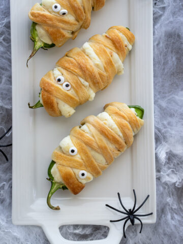 Easy Mummy Jalapeno Poppers for Halloween on a white platter with spiders on it.