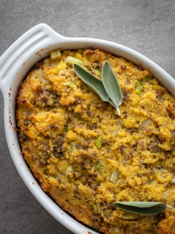 Southern Cornbread with sausage in a white baking pan and fresh sage leaves on top.