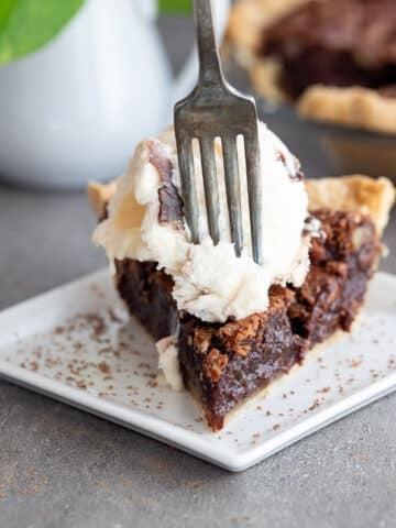 Chocolate pecan pie with ice cream on top.