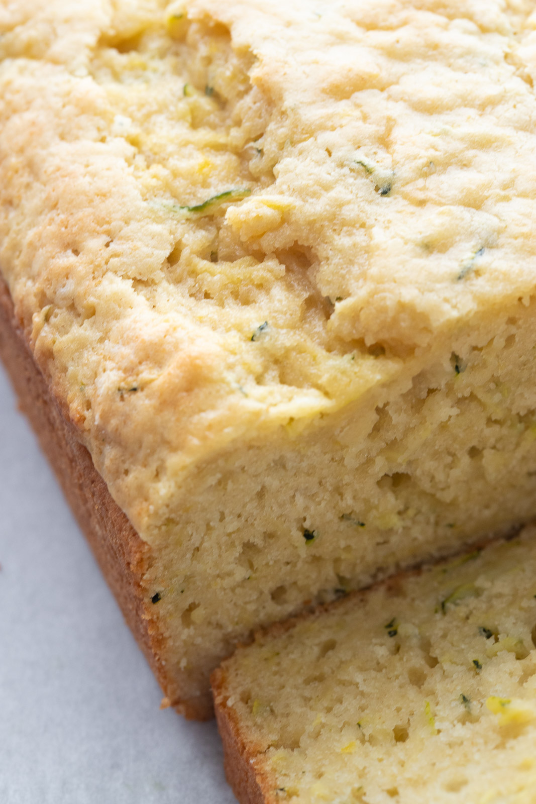 Lemon zucchini bread sliced on a piece of parchment paper.