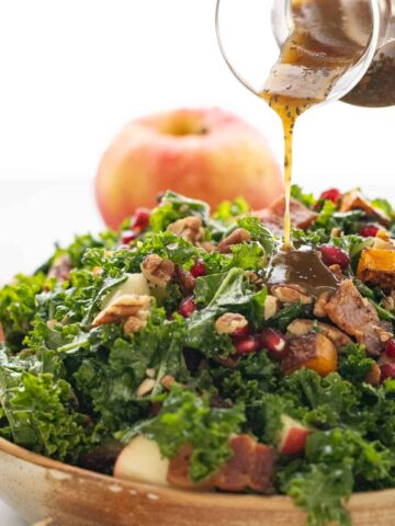 Woman pouring maple dressing over a Autumn Kale Salad with Butternut.