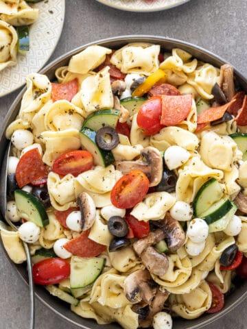Easy Tuscan Tortellini Salad in a ceramic bowl.