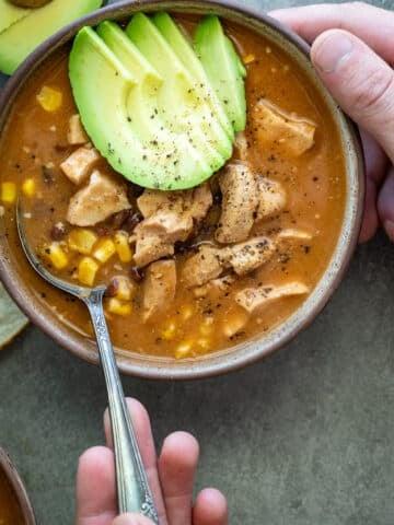 Instant Pot Chicken Enchilada Soup in a ceramic bowl.