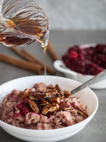 Woman pouring maple syrup over cranberry oatmeal.