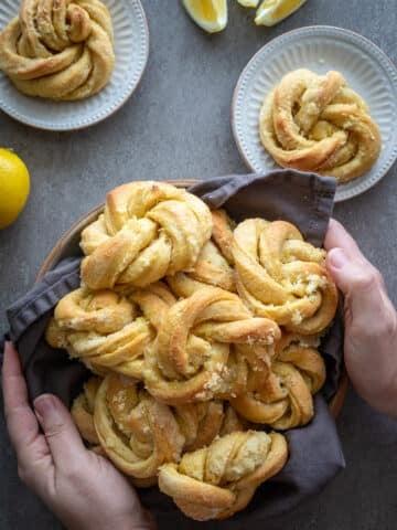 Woman holding a basket of lemon brioche rolls.