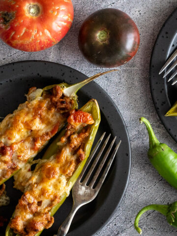 Anaheim Stuffed Peppers on black plates with antique forks.