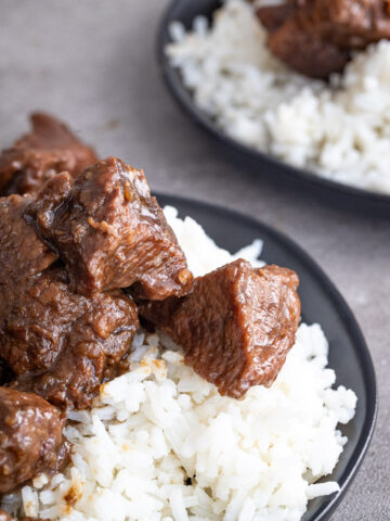 Tender balsamic beef served over rice on a black plate.